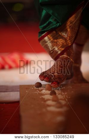 The last steps of the bride among the 7 taken during a traditional hindu religious wedding consisting of a betelnut and rice.