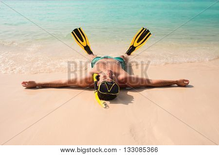 Man relaxing on the white sand beach in the clear sea water lying on the water with yellow and black flippers fins and mask. After snorkeling Maldives beach Young