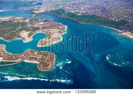 Aerial photo of Pulau Serangan ( turtle island ) with sand beach, surfing spots, sailing yacht and fisher boats at anchor in sea bay harbour and part of Denpasar and Sanur on Bali island, Indonesia