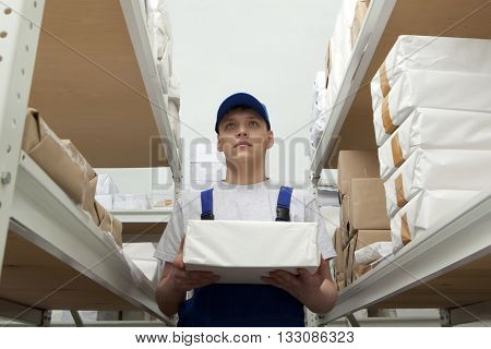 Wholesale, logistic, people and export concept - man with package  in uniform at warehouse