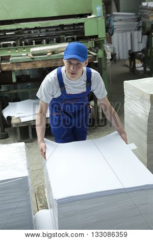 Stock offset paper.  Young man in cap working in print factory