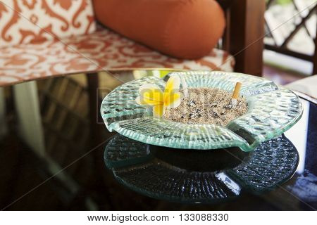 Cigarette and glass hotel ashtray on table with frangipani flower