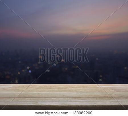 Empty wooden table with blurred aerial view of cityscape on warm light sundown for your product display montage