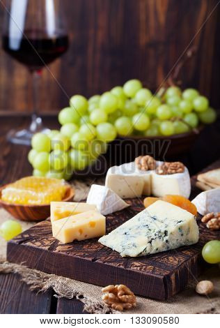 Red wine in glass with cheese, honey, nuts and grape on a cutting board wooden background