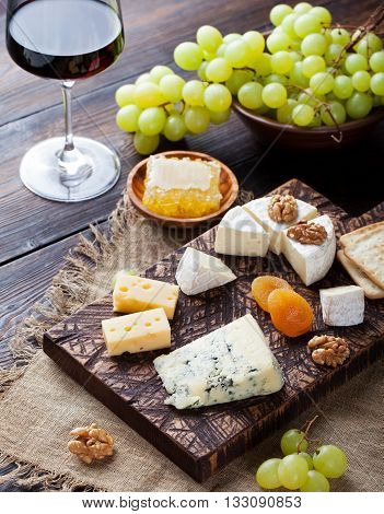 Red wine in glass with cheese honey nuts and grape
