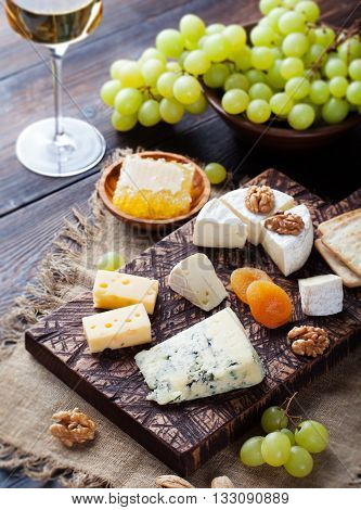 White wine in glass with cheese, honey, nuts and grape on a cutting board wooden background