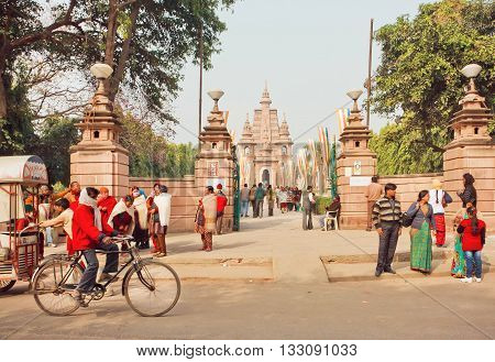 SARNATH, INDIA - JAN 5, 2016: Tourists pilgrims and cyclists going past famous Buddhist temple Mulagandhakuti Vihara on January 5, 2016. Sarnath is where Gautama Buddha first taught the Dharma at 500 BC.