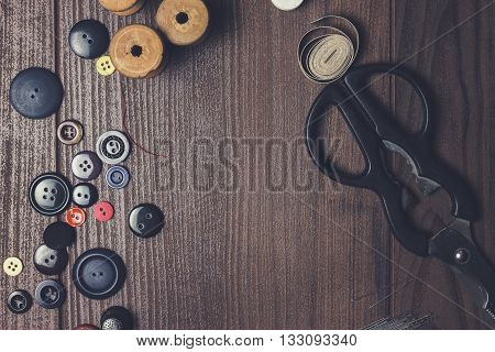 threads buttons and needles on brown wooden table