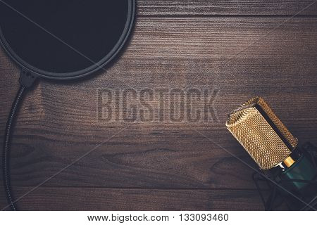 vintage condensing microphone and pop filter on wooden background