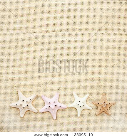 Background with four starfishes on canvas texture