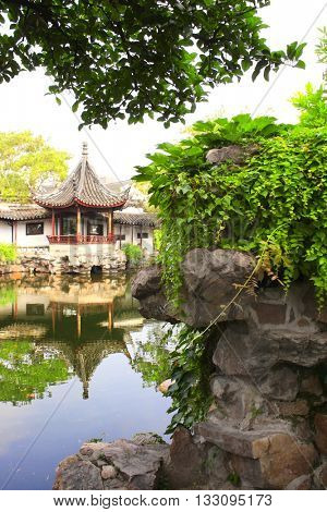 Ancient pavilion and pond with fish in Garden of Fisherman, Suzhou, China. Summer day