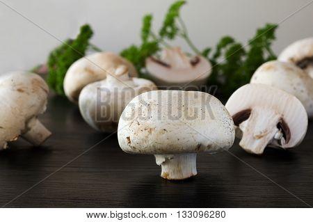 fresh champignons on a dark wooden background