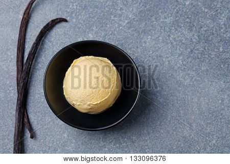Homemade vanilla caramel ice cream in black bowl with vanilla pods. Organic product on a grey stone background Top view Copy space