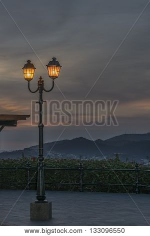 Sunset scene with antique lamp as the main subject and mountains at background in Cerro del Carmen Guayaquil Ecuador