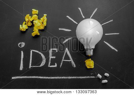 Light bulb with rays on the black chalkboard with title idea! written by white chalk and crumpled yellow papers light bulb idea business idea business concept Innovation concept
