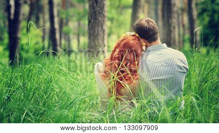 Back side of a peaceful couple sitting on a grass in the forest, enjoying beauty of nature, love and togetherness concept