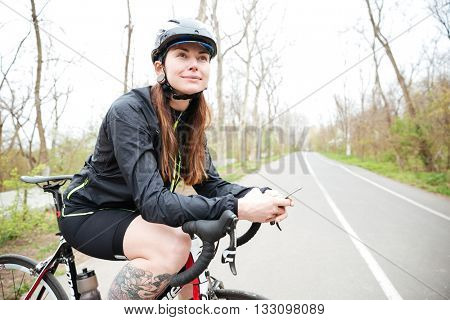 Smiling attractive young woman in bicycle helmet on bike using smartphone