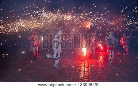 Traditional correfocs (fire runs) performance (Spanish: Baile de Diablos Catalan: Ball de Diables or Correfocs). Group of people dressed as devils and dancing with lighting fireworks fixed on devil's pitchforks. Reus Spain.