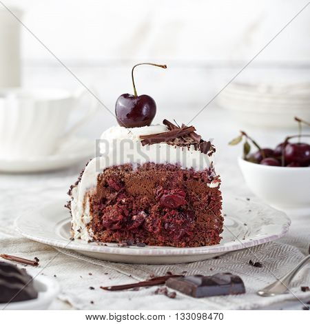 Black forest cake decorated with whipped cream and cherries Schwarzwald pie dark chocolate and cherry dessert on a white wooden background