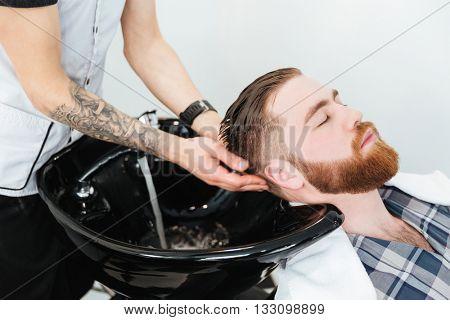 Barber washing head client in barbershop