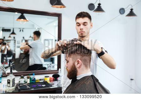 Barber cutting hair with scissors to his client in barbershop