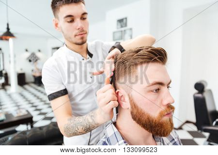 Barber combing hair to his client in barbershop