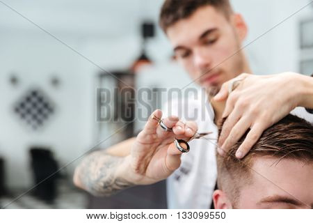 Male hairdresser cutting hair with scissors to his client in barbershop