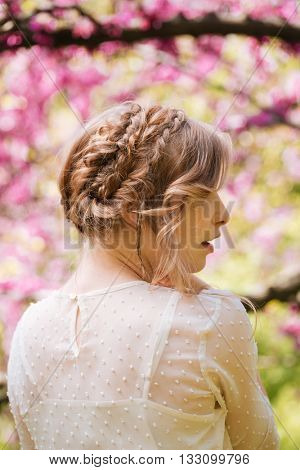 Back view of sensual attractive young woman with braids standing in blooming garden