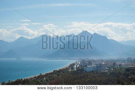 sea coastline, city and fog mountain background