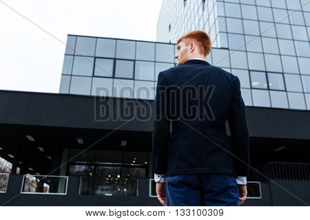 Back view portrait of a young businessman standing outdoors with glass building on background