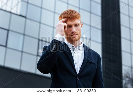 Businessman thinking about something outdoors with glass building on background