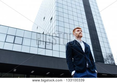 Confident redhead businessman standing with glass building on background
