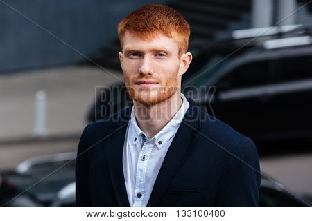 Handsome redhead businessman looking at camera outdoors