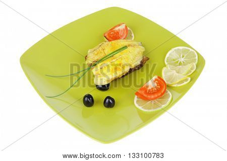 Roast sea sole fish fillet served on bread with tomatoes, olives and chives on green plate isolated over white background