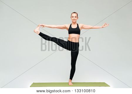 Pacified young woman standing and practicing yoga