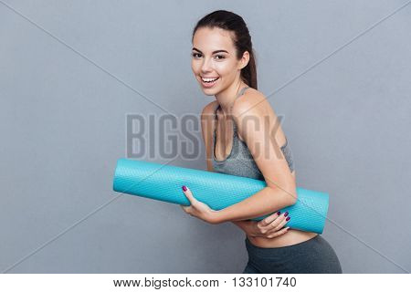 Attractive laughing sportswoman holding yoga mat isolated over grey background