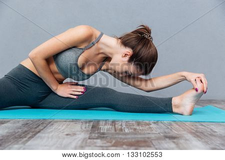 Young healthy fitness woman doing splits isolated on grey background