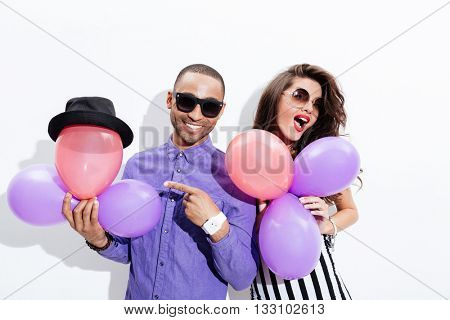 Young silly couple in sunglasses holding balloons having fun isolated on white background