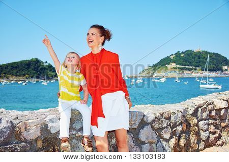 Happy Mother And Child Pointing Up In Front Of Lagoon