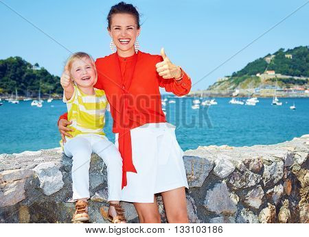 Mother And Daughter Showing Thumbs Up In Front Of Lagoon