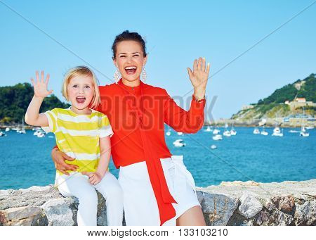 Smiling Mother And Daughter Handwaving In Front Of Lagoon