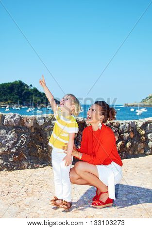Mother And Daughter Pointing On Something In Front Of Lagoon