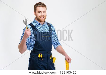 Portrait of a smiling male builder standing with equipment isolated on a white background