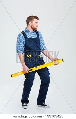 Full length portrait of a funny male builder holding waterpas isolated on a white background