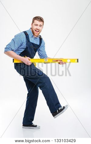 Full length portrait of a cheerful male builder playing with waterpas isolated on a white background