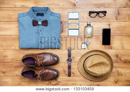 Travel concept shoes, shirt, mobile phone, watch, lighter, perfume, eyeglasses, hat on the desk