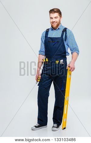 Full length portrait of a handsome male builder standing isolated on a white background