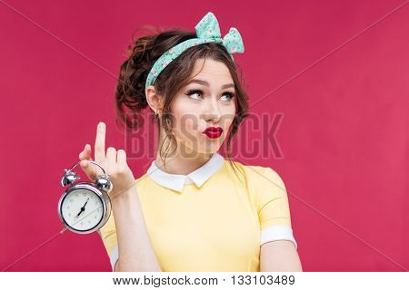 Unhappy pretty young woman holding alarm clock over pink background