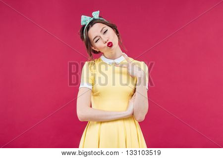 Pretty playful pinup girl winking and sending a kiss over pink background