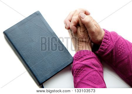 An old person praying with the Holy Bible by her
